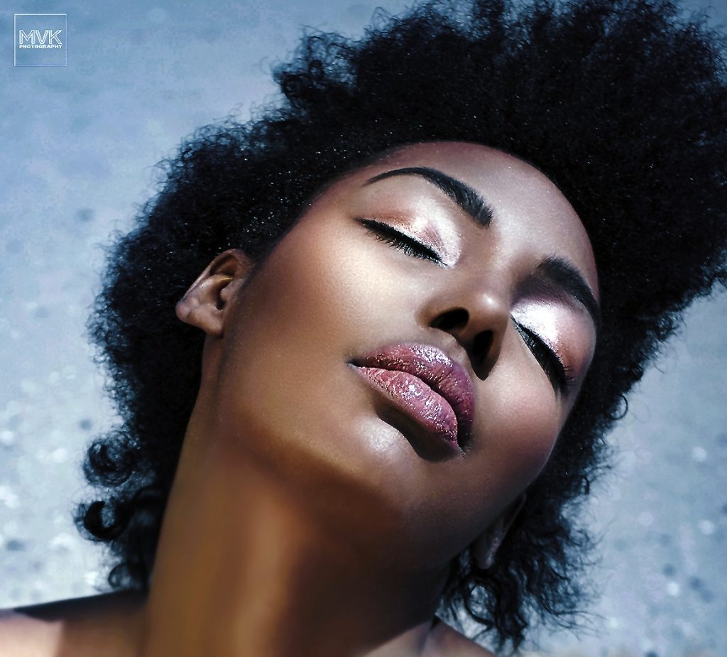 Black model on beach with shimmery eyeshadow and lipgloss